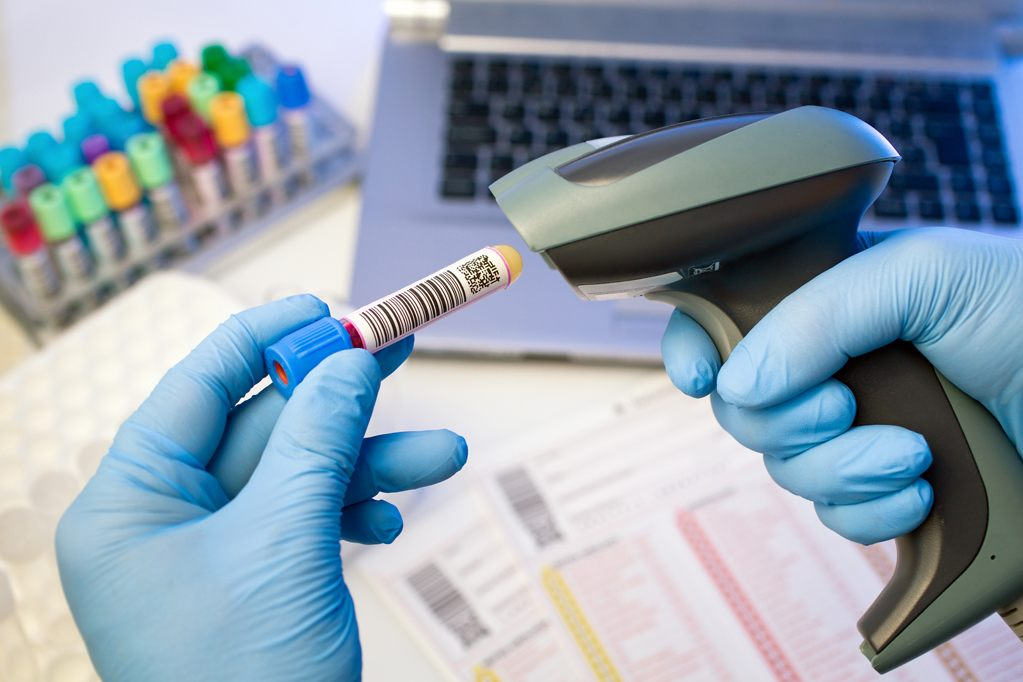 technician hands scanning barcodes on biological sample tube in the lab of blood bank